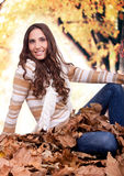 Beautiful autumn woman sitting on leaves outdoor Royalty Free Stock Images