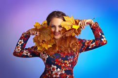 Beautiful autumn woman with yellow maple leaves. Beautiful autumn woman in studio with yellow maple leaves Royalty Free Stock Image