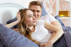 Beautiful awakened loving couple in bed in the morning. Young adult heterosexual couple lying on bed in bedroom royalty free stock photography