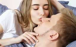 Beautiful awakened loving couple in bed in the morning. Young adult heterosexual couple lying on bed in bedroom royalty free stock photo