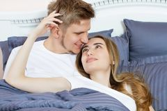 Beautiful awakened loving couple in bed in the morning. Young adult heterosexual couple lying on bed in bedroom.  royalty free stock image