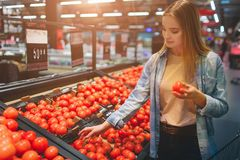 Beautiful and awesome lady is at grossary store and choosing some tomatoes to buy. She has chosen one tomato and hold it. In her hand. Close up Stock Photography