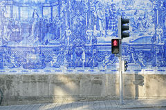 Beautiful azulejos and traffic light in Porto. External wall of a church in Porto, Portugal. The wall is richly adorned by azulejos painted in blue. In front of Royalty Free Stock Images
