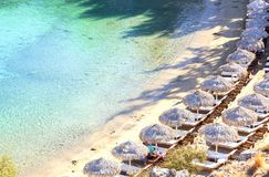 Beautiful azure beach and deck chairs, top view. The seaside res Stock Photos