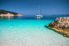 Beautiful azure blue lagoon with sailing catamaran yacht boat at anchor. Pure white pebble beach, some rocks in the sea.  royalty free stock photos