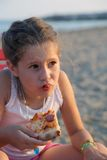 Beautiful babe eats a slice of pizza on the beach Stock Images