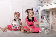 Beautiful babies playing on   floor at   Christmas tree. Royalty Free Stock Image