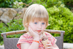 Beautiful baby. Young girl eating in restaurant Stock Photo