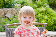 Beautiful baby. Young girl eating in restaurant Stock Image
