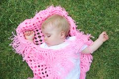 beautiful baby asleep with blanket on green gras Royalty Free Stock Photo