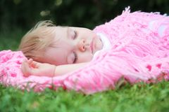 Beautiful baby asleep with blanket on green gras Royalty Free Stock Photos