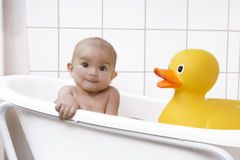 Beautiful baby in a bath tub. Cute baby girl sitting in a bathtub with a rubber duck Royalty Free Stock Images