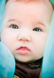 Beautiful Baby with Blue. A beautiful baby surrounded by blue looking into the camera with curiousity Stock Photography