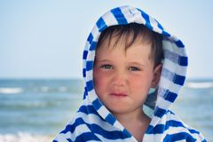 Beautiful baby with blue eyes on the sea background smiling, sweet and gentle. Cute child with atopic dermatitis. On the background of the sea Royalty Free Stock Photos