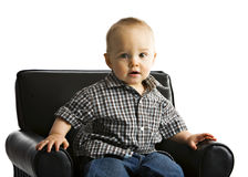 Beautiful Baby Boy. A beautiful baby boy getting up from a child's overstuffed chair.  Isolated on white Stock Photography