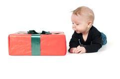 Beautiful baby boy and big christmas present. On white Stock Photography