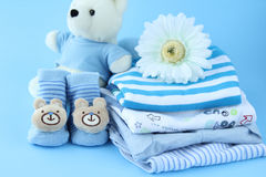 Beautiful baby boy clothes. Stack of  clothes  for baby boy on blue background with toy and flower Royalty Free Stock Image