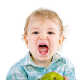 Beautiful baby boy eats green apple. Stock Photos