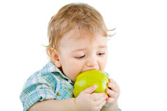 Beautiful baby boy eats green apple. Stock Images
