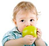 Beautiful baby boy eats green apple. Royalty Free Stock Photography