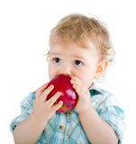 Beautiful baby boy eats red apple. Royalty Free Stock Image