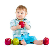 Beautiful baby boy eats red apple. Royalty Free Stock Photography