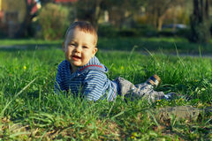 Beautiful baby boy lying on green grass. Beautiful baby boy lying among green grass on spring lawn Royalty Free Stock Photography