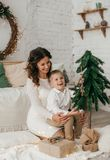 Beautiful baby boy near a Christmas tree with gifts stock photos