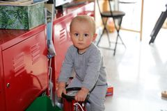 Beautiful Baby Boy Playing With Firefighter Ride-On. Cute Baby Boy Playing With Firefighter Ride-On Toy Car At Home, Close Up Portrait royalty free stock photo