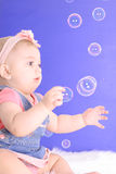 Beautiful baby catching bubbles Royalty Free Stock Photos