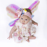 Beautiful baby fairy. Cute baby girl dressed in a flower dress and butterfly wings looking up. Isolated on white Stock Photos