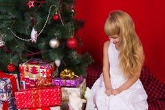 Beautiful baby gir near the Christmas tree in New Years Eve Stock Image