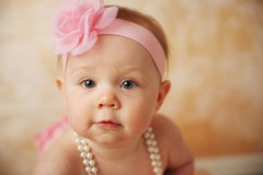 Beautiful baby girl. Adorable young baby girl wearing a vintage pearl necklace and pink rose headband Stock Image