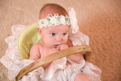 A beautiful baby girl. With cute facial expression lying in a basket Royalty Free Stock Image