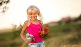 Beautiful baby girl blonde with soft toys in a field in summer stock images