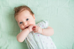 Beautiful baby girl with blue eyes playing on a knitted mint blanket Royalty Free Stock Photography