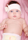 Beautiful baby girl with bow in hair smiling a happy smile Stock Images