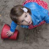 Beautiful baby girl with brown eyes. Beautiful little girl with brown eyes in the sand box Stock Photos