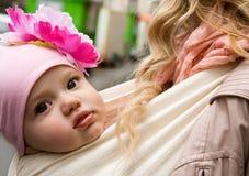 Beautiful baby girl carried in sling. Beautiful baby girl carried by her mother in sling stock images