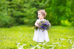 Beautiful baby girl carrying flowers in a garden. Beautiful baby girl with curly hair carrying flowers in a garden Royalty Free Stock Image