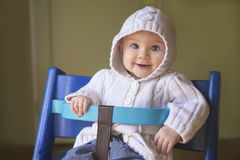 Beautiful baby girl in a chair. Adorable baby girl in a white hoodie sitting in a baby chair and smiling into the camera Stock Photo