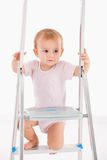 Beautiful baby girl climbing on ladder Stock Photo