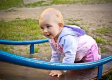 Beautiful baby girl climbing a slide in playground Royalty Free Stock Photography
