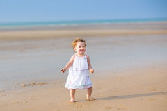 Beautiful baby girl with curly hair on tropical beach Royalty Free Stock Photography