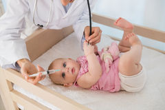 Beautiful baby girl with doctor using syringue and needle Royalty Free Stock Image