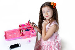Beautiful baby girl doing makeup and lipstick in a dress isolate Royalty Free Stock Images