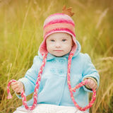 Beautiful baby girl with Down syndrome sitting in autumn park. Beautiful girl with Down syndrome sitting in autumn park Stock Image