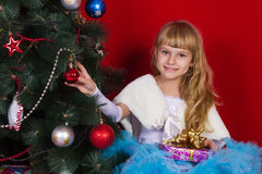 Beautiful baby girl in a dress and in New Year's Eve smiling and looking for a gift Stock Images