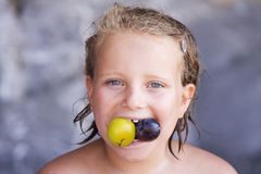 Beautiful baby girl eating a plum Stock Photography