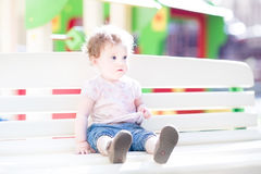 Beautiful baby girl enjoying sun on playground Royalty Free Stock Images